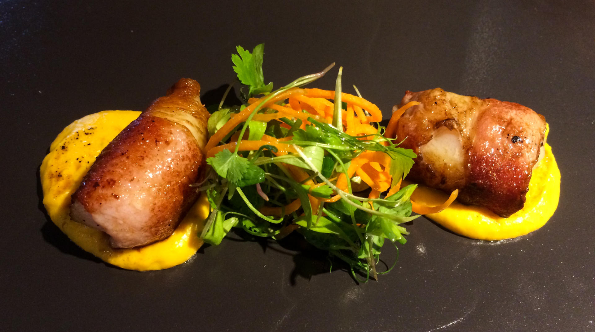 bacon wrapped scallops on a bed of pureed squash served with salad