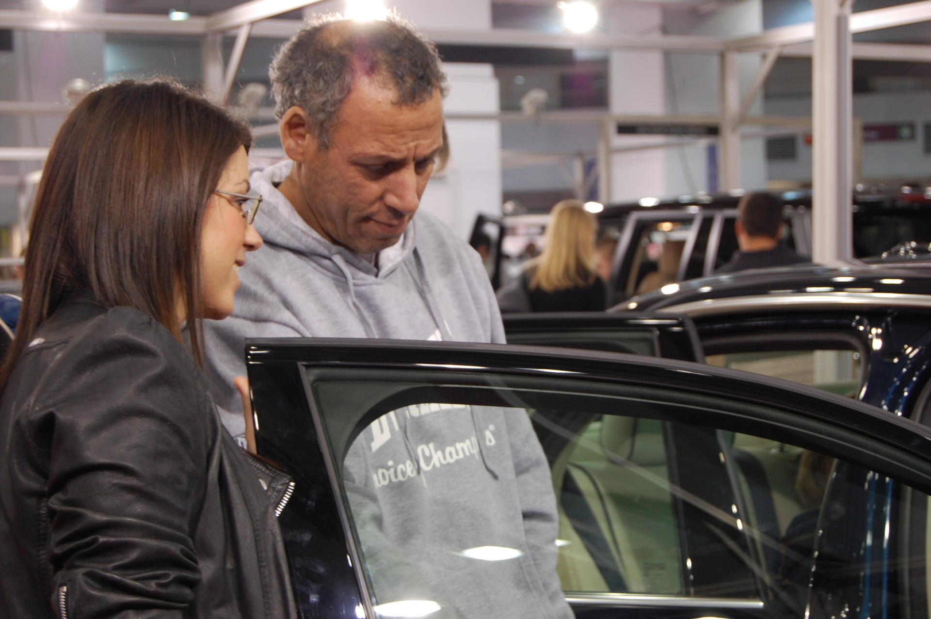 Two people looking at the inside of a car.