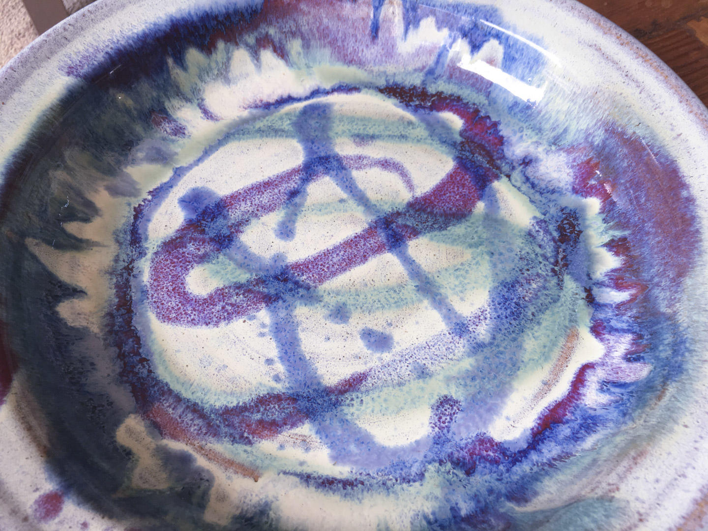 Close up of swirly purple and blue pattern on a quiche dish.