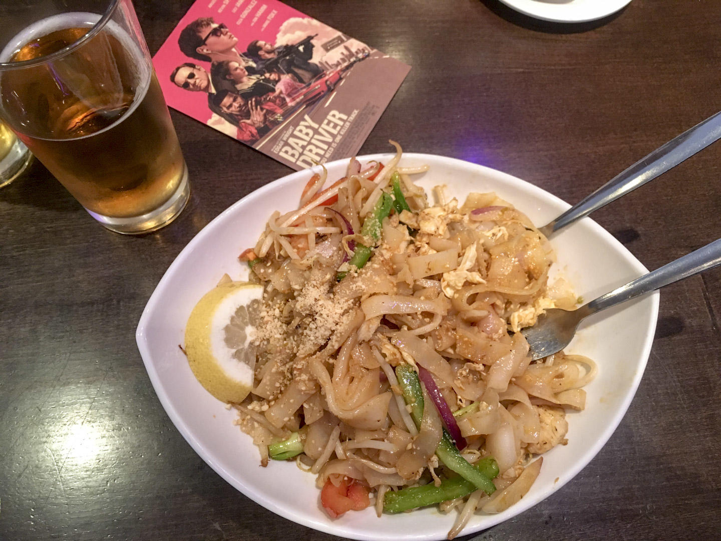 Birds eye view of a pad thai noodle dish with a half pint of king fisher beer.