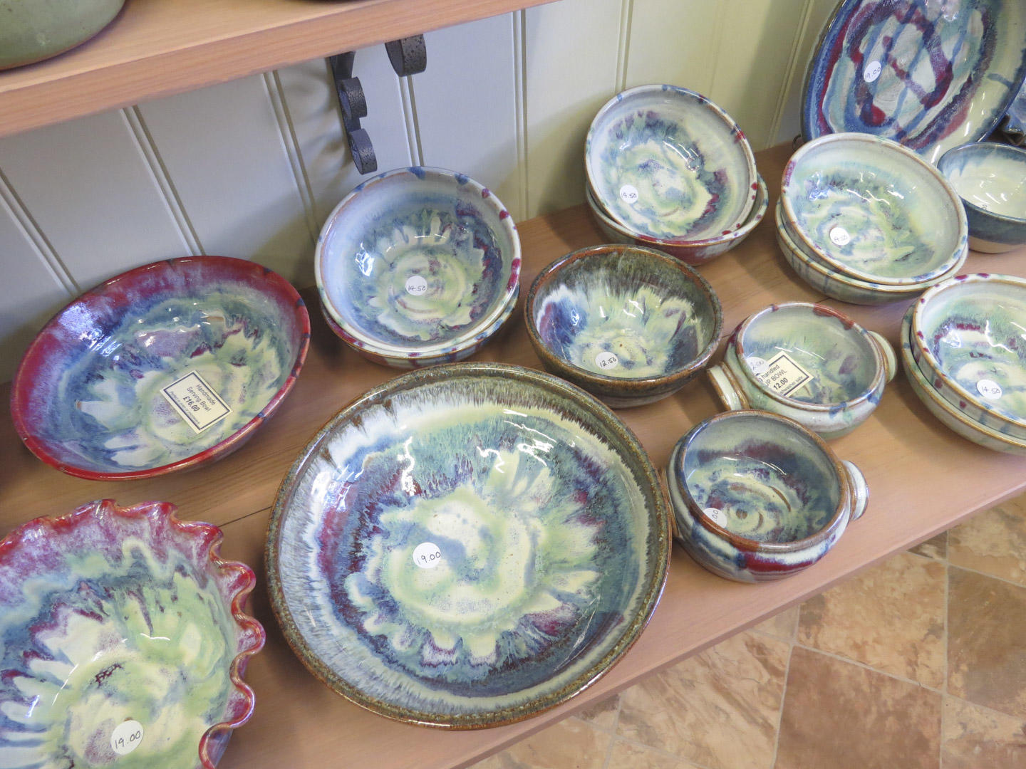 Handmade bowls of different sizes on a shelf.