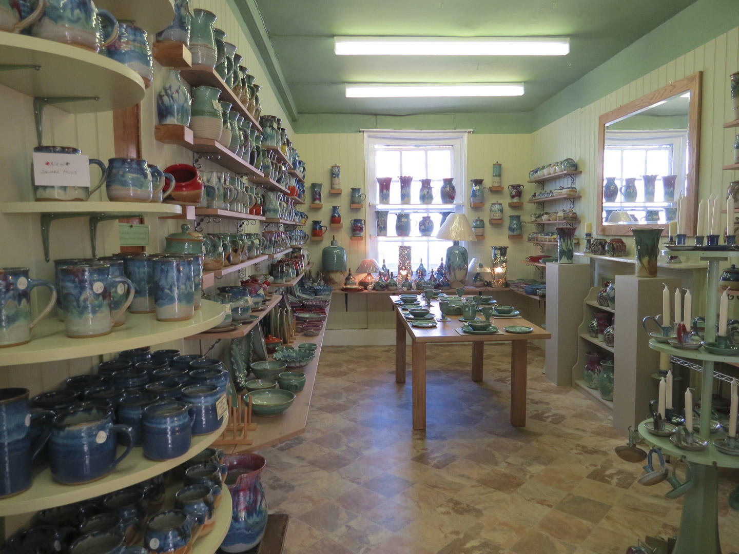 First floor of the Canterbury Pottery store showing lots of mugs and pots on shelves.