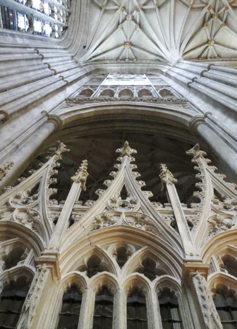 Looking up at Canterbury Cathedral's ceiling with gothic spires at the bottom