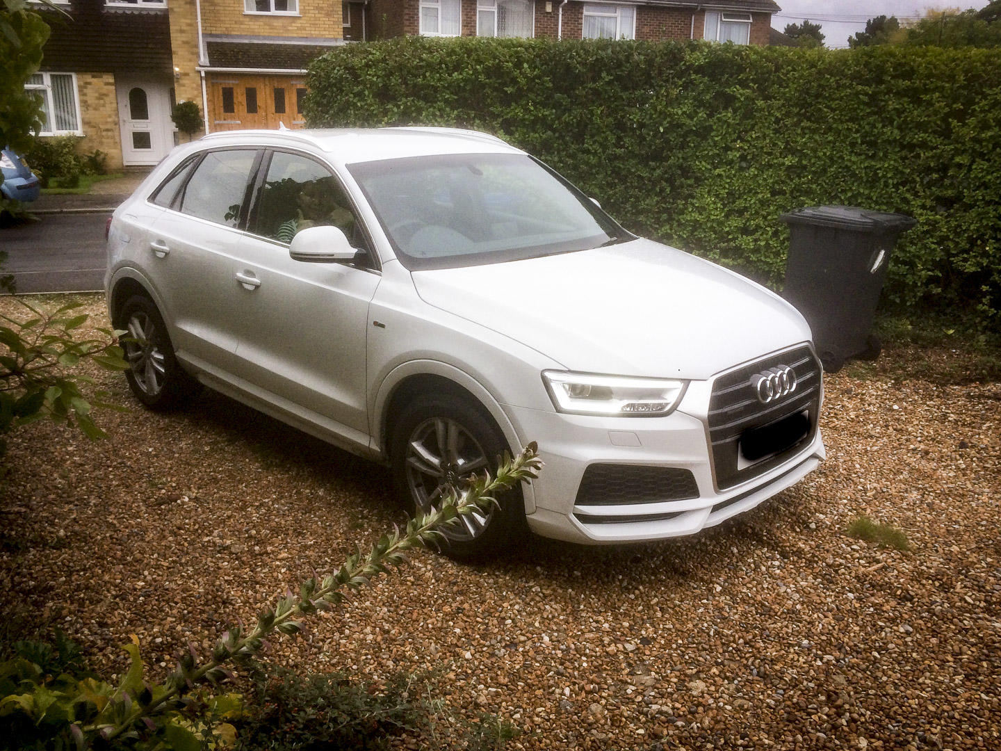 Glacier white Audi Q3 front side on view on driveway.
