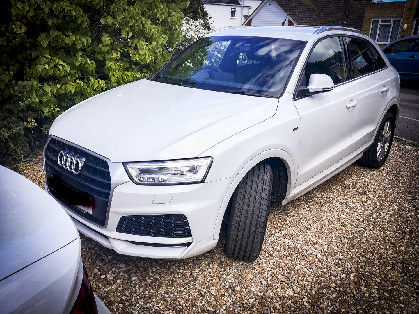 Glacier White Audi Q3 front side on view on a driveway.