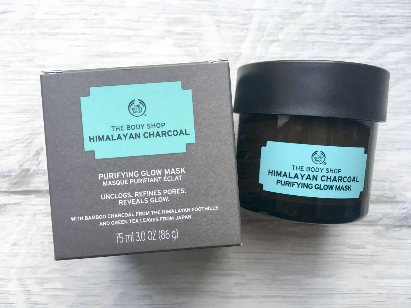 The Body Shop Himalayan Charcoal Purifying Glow Mask flat lay photograph