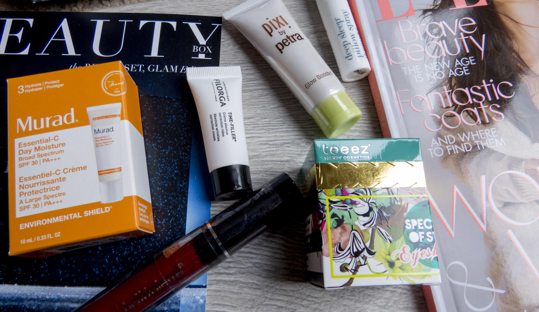 A flatlay with various products and magazines from the November Lookfantastic beauty box.